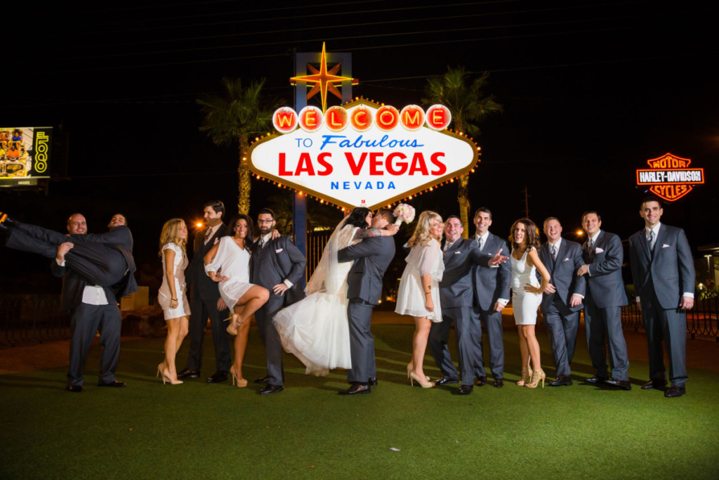 wedding party in front of welcome to las vegas sign