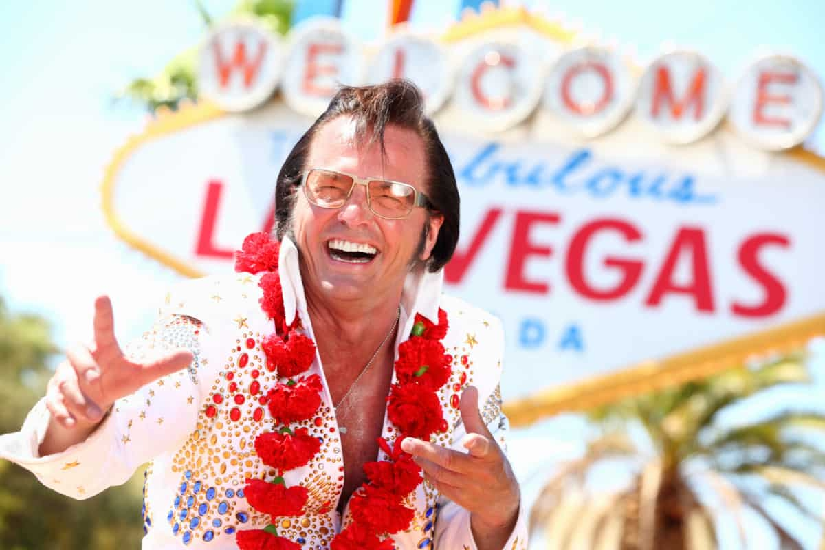 Elvis impersonator in front of welcome to las vegas sign