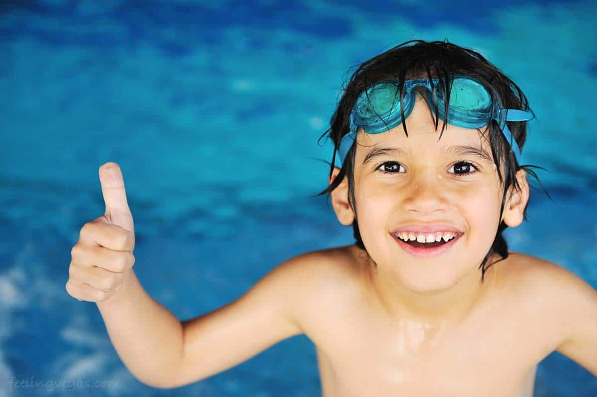 Young boy giving a thumbs up at the indoor swimming pool