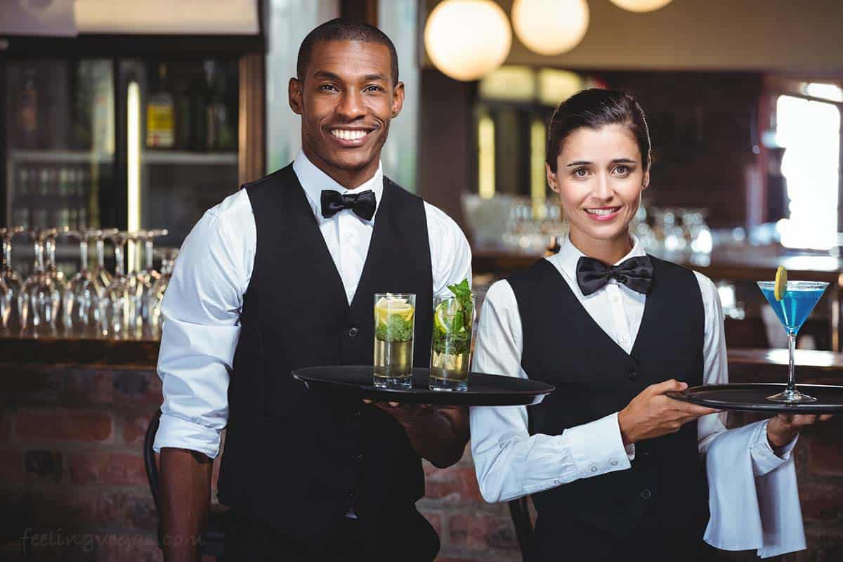 Cocktail waiter and waitress serve free drinks in a Las Vegas casino.