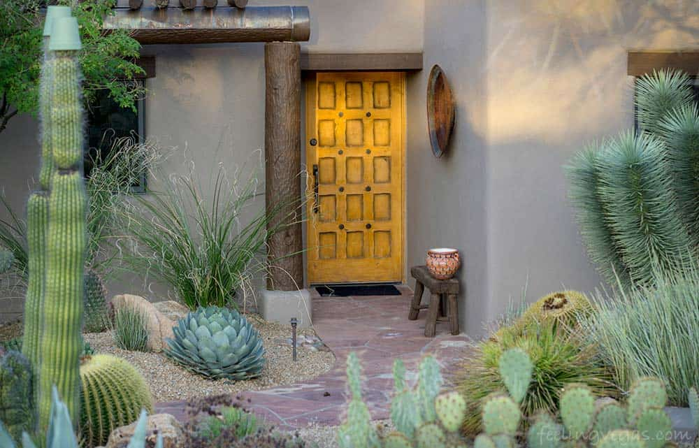 Home and yard with desert landscaping.