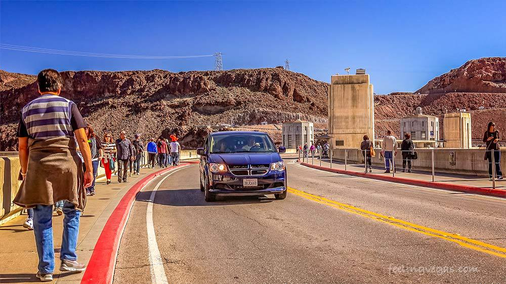 Visitors walk and drive across the Hoover Dam