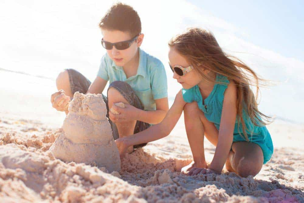 Kids building sand castle on beach in San Diego