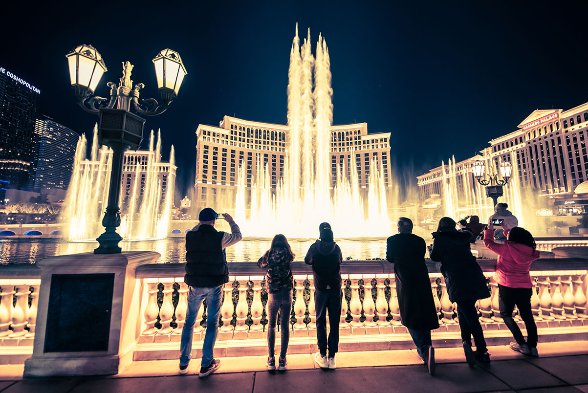 Tourists at Bellagio Fountains at night on the Las Vegas Strip.